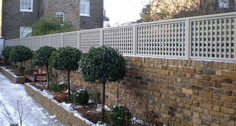Garden Wall Fencing Trellis Painted Light Grey On Top Of Brick Wall Raised