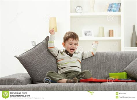 kids on couch happy kid with toys sitting on sofa hands in air stock
