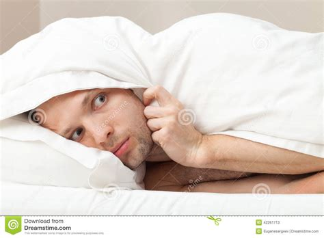 man in bed portrait of funny scared young man in bed stock photo