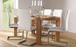 Dining room equipped with modern white chairs and wooden table