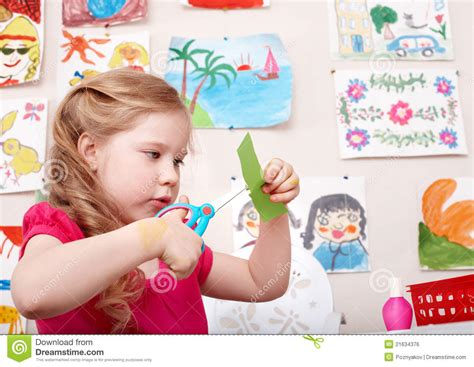 Paper With Children - child with scissors cut paper in play room stock photo