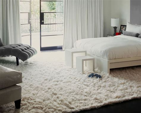modern bedroom with large white rug bed and