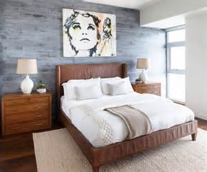 Leather bed with cream and beige bedding grey wood accent wall