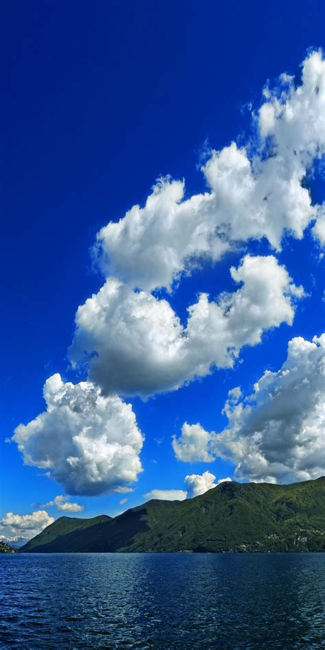 white clouds blue sky mountains sea nature