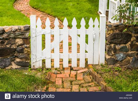 white wooden gate a white wooden picket gate in a low wall across a