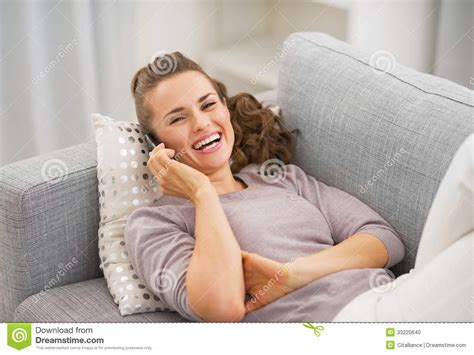 laying on couch smiling young woman talking mobile phone while laying on