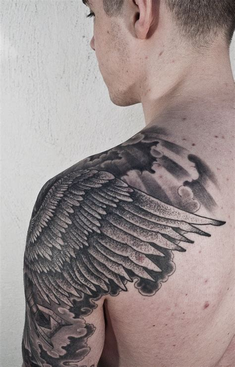 wing shoulder tattoo wing tip wrapped around shoulder tatts