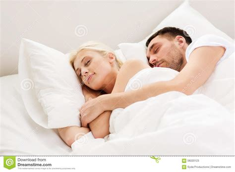 someone sleeping in my bed happy couple sleeping in bed at home stock photo image