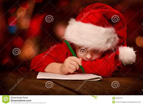 christmas child writing letter in red santa hat stock