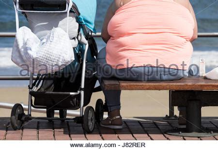 fat lady on bench bottom of an obese fat woman sitting on a bench stockfoto