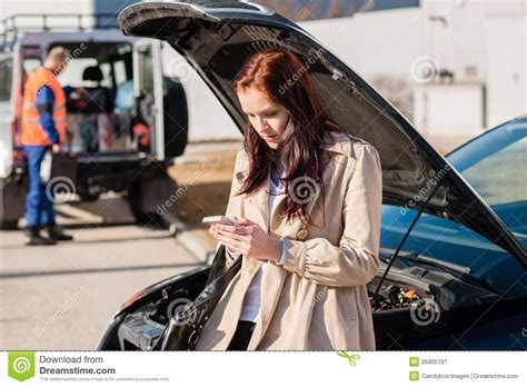 woman driver on the phone for car breakdown woman dialing her phone after car breakdown stock image