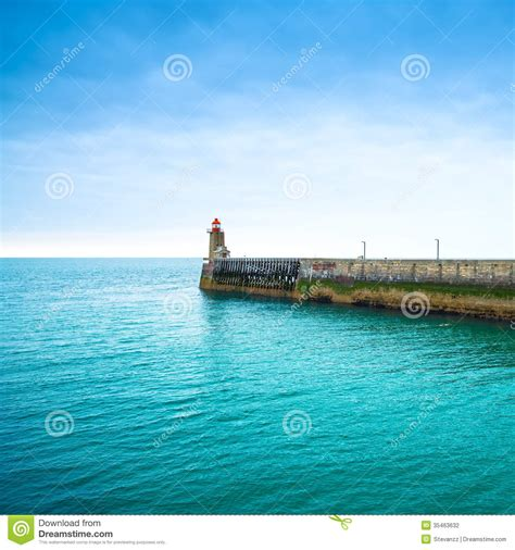pier in french pier and lighthouse on sunset fec harbor normandy