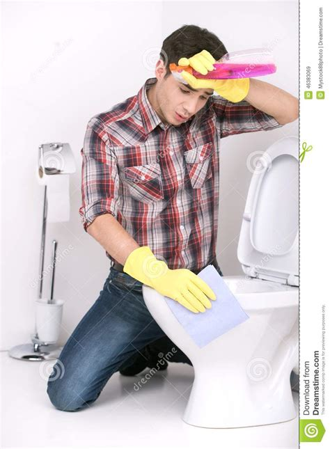 man cleaning bathroom man cleaning toilet with spray cleaner stock image