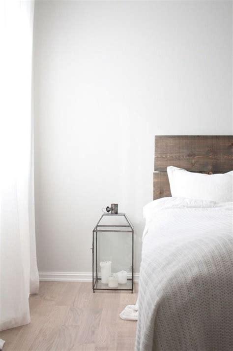 light wood headboard light grey walls light wooden floor white curtains grey