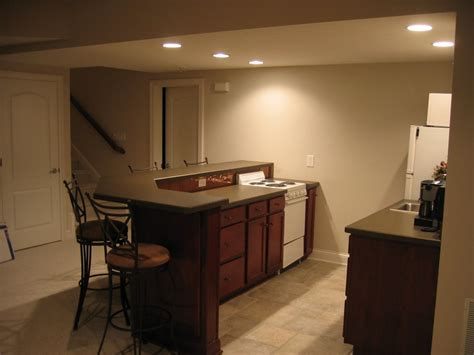 Warm beige home basement bar interior designs with gorgeous tier bar table units feat four