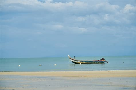 floating boat photo boat floating on the beach photo free download