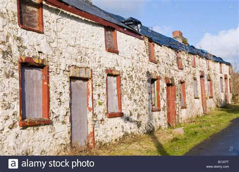 boarded up derelict row of 4 terraced cottages for