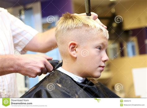 cutting boy hair with scissors hairdresser trimming blonde hair of young boy stock photo