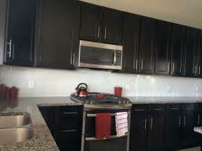 white glass subway tile backsplash with dark cabinets