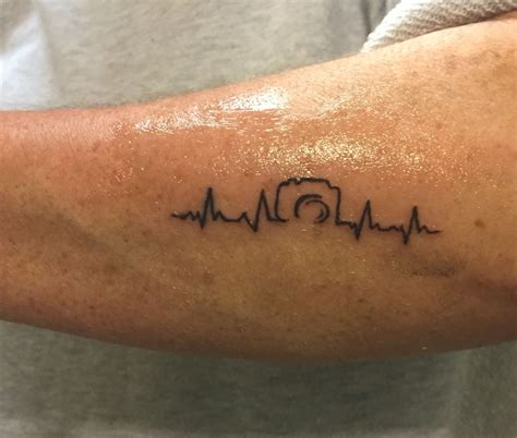 small camera tattoo with heartbeat photography
