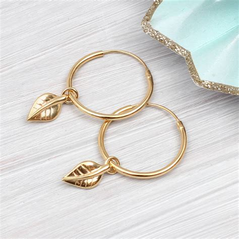 gold hoop and leaf charm earrings by hurleyburley