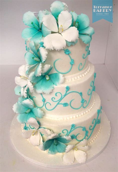 Teal and white wedding cake decorated with a big and