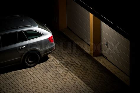 Night view of a car parked in front of the garage   Stock