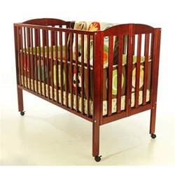 folding size crib in cherry