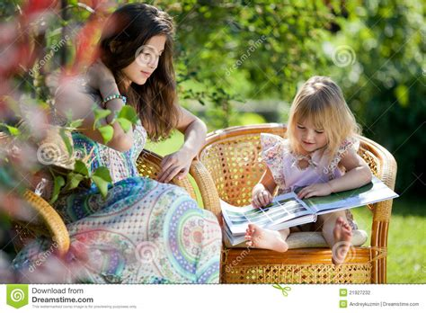 girl reading book sitting  wicker chairs outdoor stock