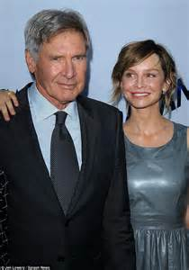 harrison ford flashes a smile as he s joined at