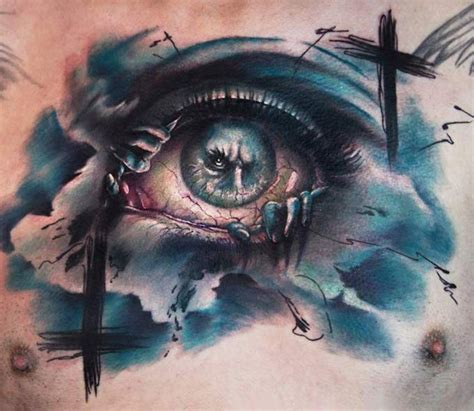 cross tattoo by eye abstract style colored chest of creepy looking eye