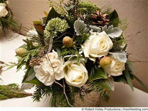 Winter centerpiece with evergreens, white roses, and pine