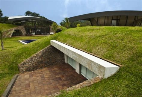 two homes tucked in the ground are topped with sweeping