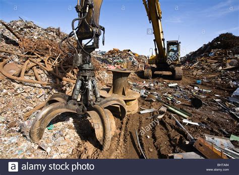 excavating machine with large grapple claw at scrap