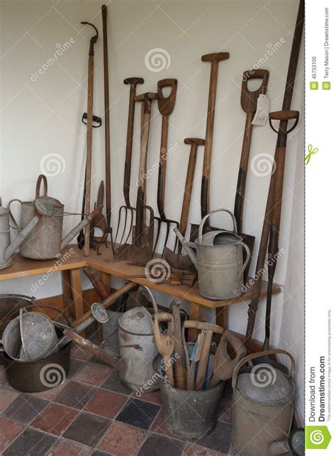Decorative Watering Cans vintage garden tools in white brick shed stock photo