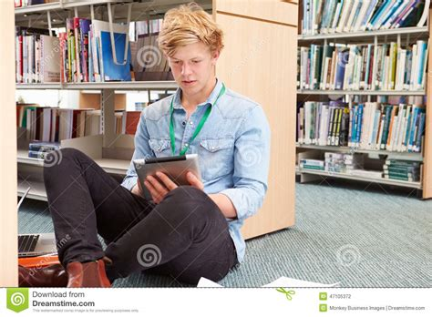 male architect with digital tablet studying plans in male college student studying in library with digital