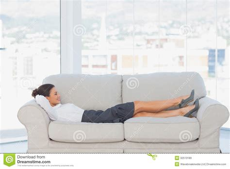 lay down on the couch smiling business woman lying down on the couch royalty