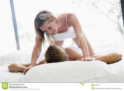 lying in bed couple lying in bed being playful and smiling stock image