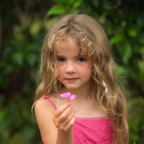 very young little girls but very young girl faces young girl holding pink flower at