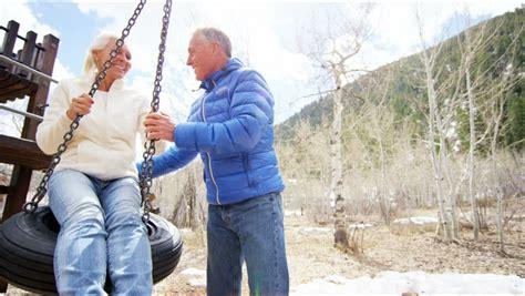 old people swinging aspen sun flare caucasian usa couple seniors retired