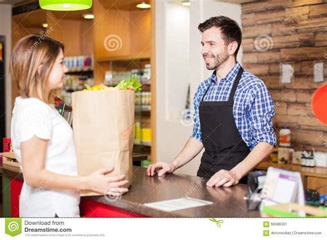 handsome cashier helping out a customer stock image