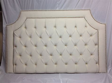 tufted upholstered headboard with brass nailheads