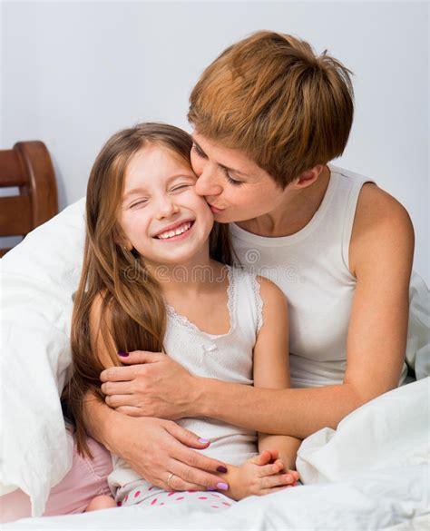 hija se mete a la cama de su padre para cpjer la mam 225 abraza y besa a la hija imagen de archivo imagen
