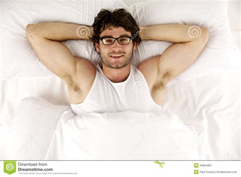 lied in bed man laid in white bed looking up at the camera smiling