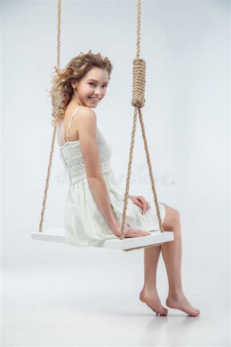 swing her beautiful smiling woman sitting on swing isolated stock