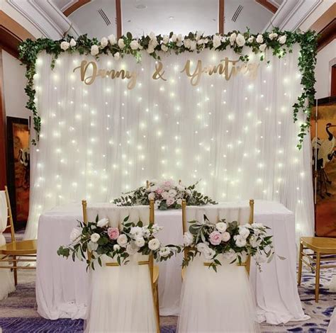 White tulle backdrop with artificial white flower foliage