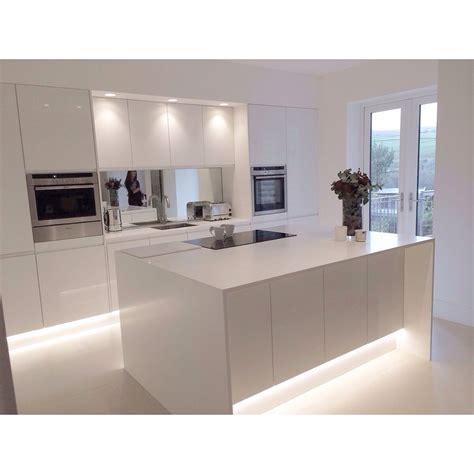 modern white gloss integrated handle kitchen with 18mm corian wrap and worktops design by