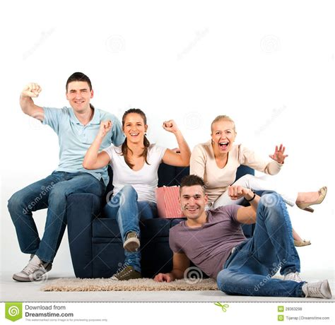 people sitting on a couch young people sitting on a sofa and cheering stock photo
