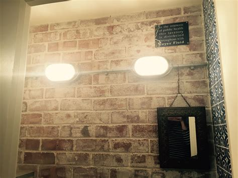 whitewashed exposed brick wall galvanised conduit lighting