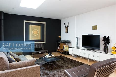black feature wall living room gap interiors contemporary living room with leather armchairs and black feature wall image